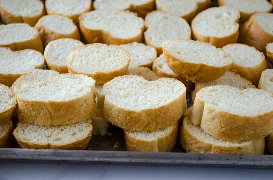 La capirotada vegana es pan tostado bañado en un almíbar de piloncillo, canela, y clavo de olor. Con plátano, cacahuates y coco rallado