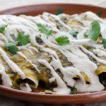 Estas enchiladas verdes veganas están rellenas con un salteado de chile poblano, cebolla, elote y frijoles pintos, con salsa verde y crema