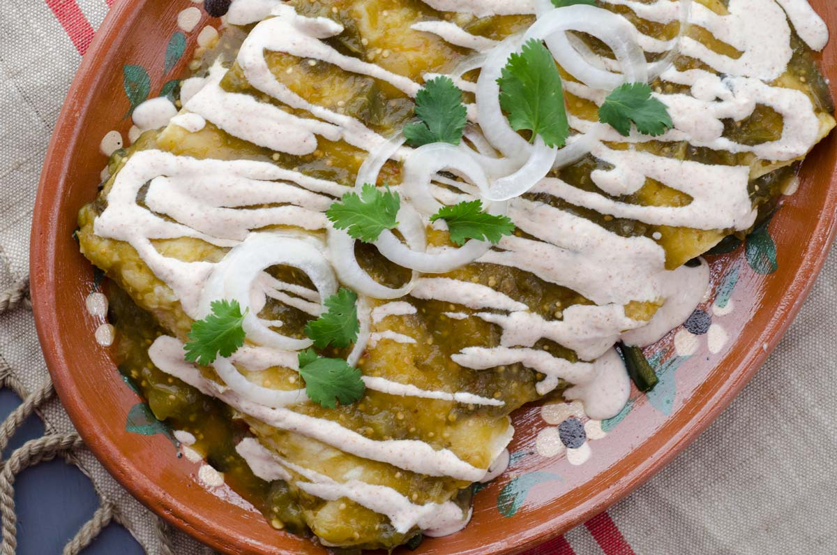 Estas enchiladas verdes veganas son unas de mis favoritas. Las tortillas se rellenan con un salteado de chile poblano, cebolla, elote y frijoles pintos. Después se bañan con una salsa de tomatillo y crema de almendras.