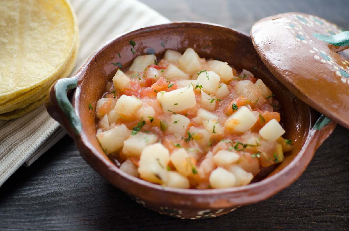 Papas Revueltas a la Mexicana. Papas cocidas en salsa servidas sobre tortillas calientas.