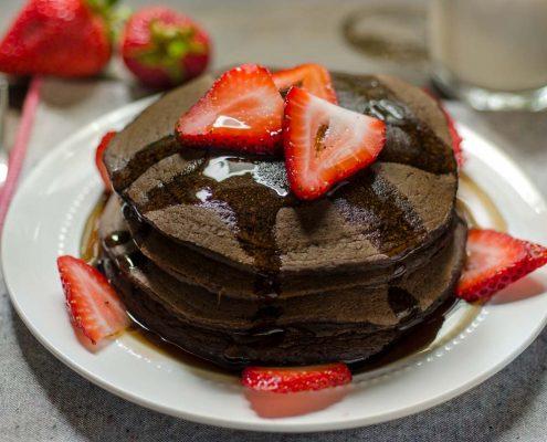 Estos hot cakes veganos de chocolate y fresa son perfectos para el desayuno! Están rellenos de fresas y espolvoreados con canela.