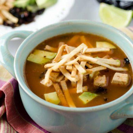 Esta sopa de tortilla vegana está sazonada con epazote, chile morita, tomate, cebolla, ajo y chile chipotle. Agrega tortillas y tofu.