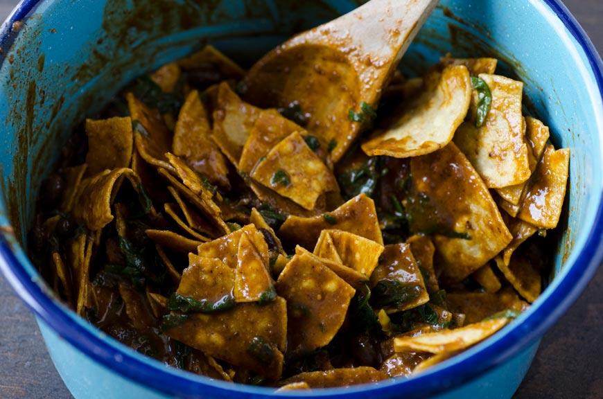 Estos chilaquiles con mole veganos están acompañados con frijoles negros, espinaca, crema de almendras y queso cotija vegano.