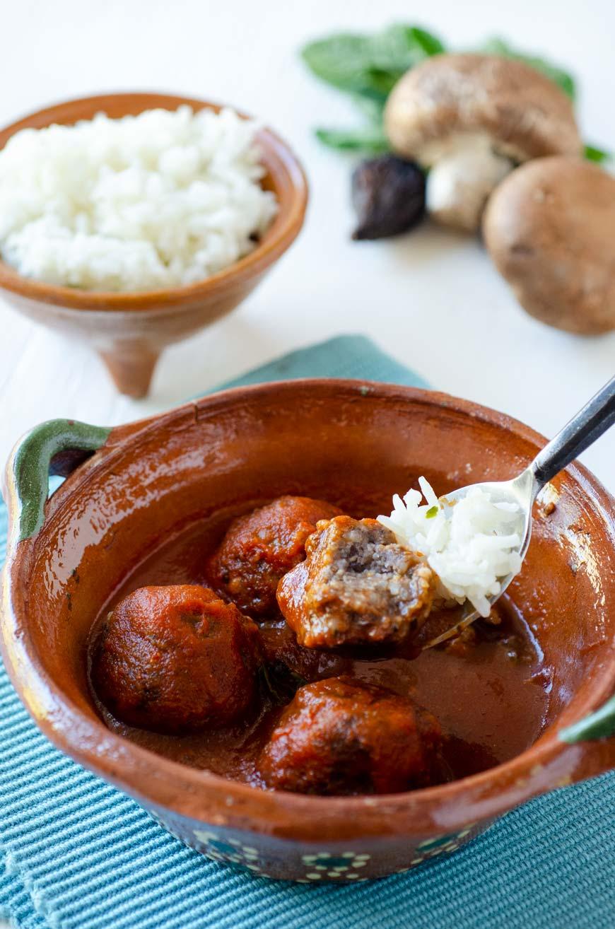Estas albóndigas veganas están hechas con una mezcla de frijoles negros, arroz y champiñones salteados, se sirven sobre un caldillo de tomate y chile ancho.