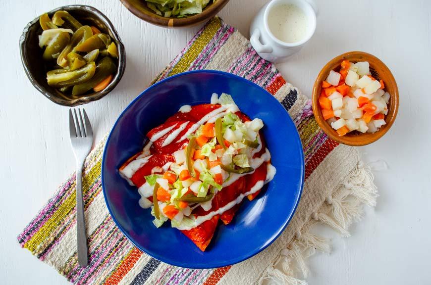 Enchiladas Mineras Veganas, rellenas de setas salteadas con una salsa de chile guajillo y papas y zanahorias, lechuga, crema y jalapeños
