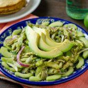 Aguachile verde vegano en un plato de talalvera azul sobre una servilleta color melon