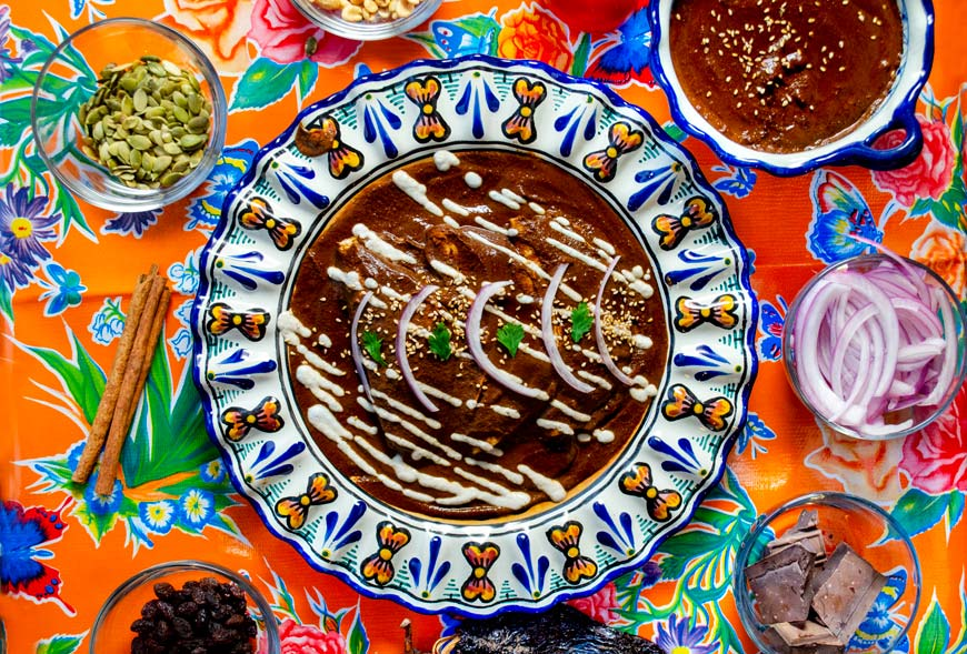 enmoladas de mole negro oaxaqueño en un plato de talavera sobre un mantel anaranjado