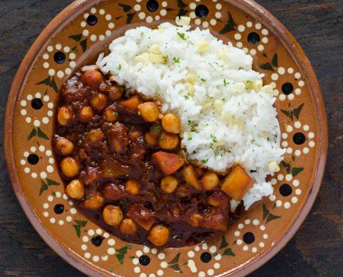 guisado de camote y garbanzos en un plato de barro con arroz blanco con elote