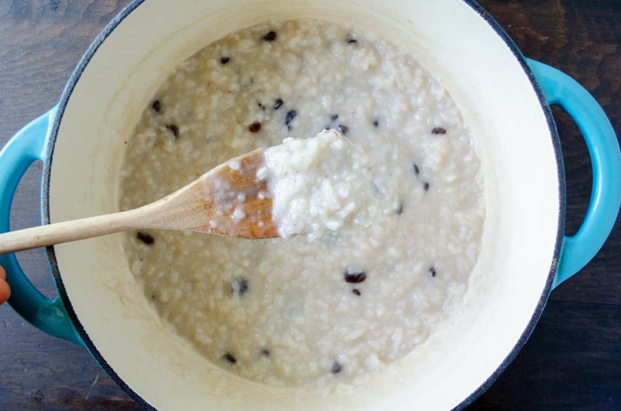 una cuchara de madera mostrando el arroz con leche vegano