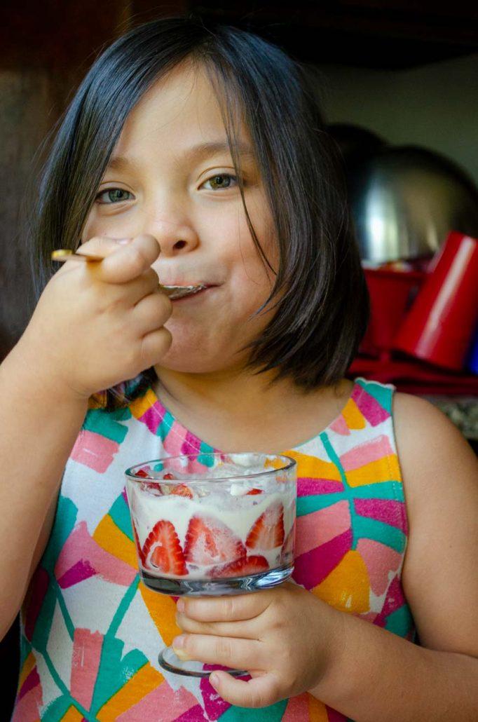 una niña en un vestido de colores comiendo fresas con crema