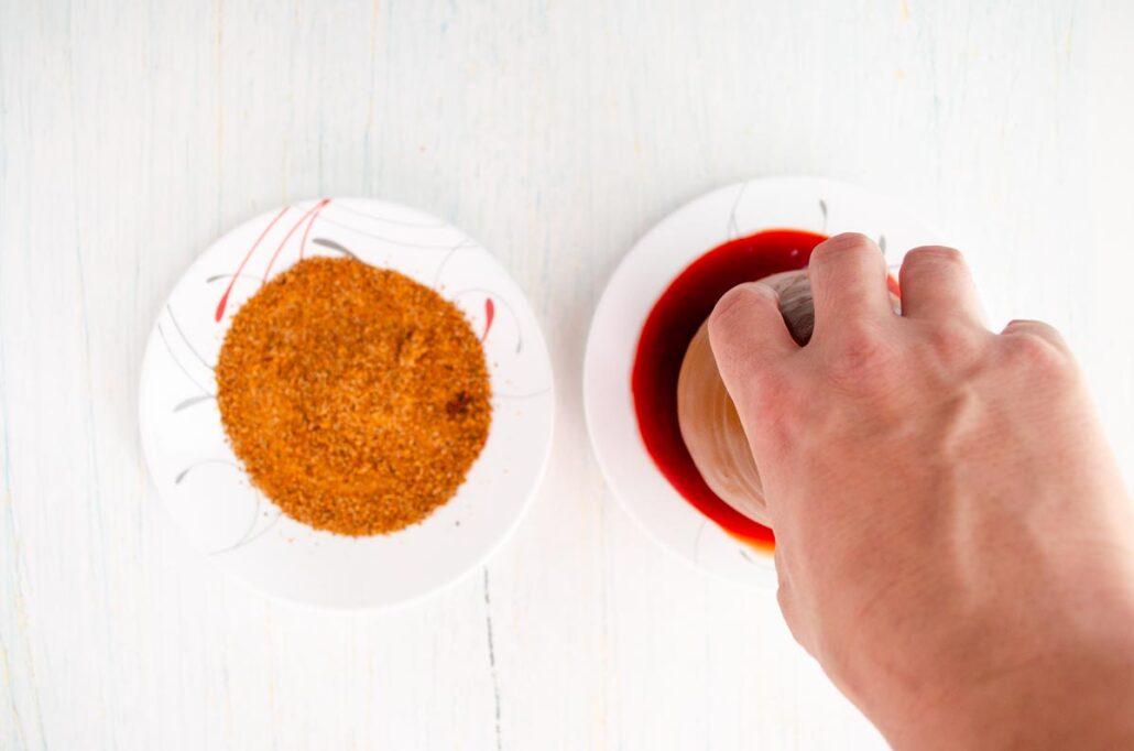 ¿Cómo escarchar jarritos locos? Coloca el chamoy y el chile piquín en dos platos separados. Sumerge el borde del jarro en el chamoy y después en el plato con chile en polvo.